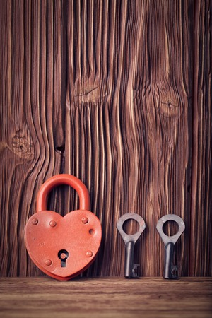 Heart shaped lock and two keys over vintage wooden background