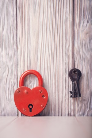 Heart shaped lock and key over light vintage wooden background
