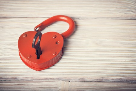 closed lock: Open heart shaped lock and key over light vintage wooden background
