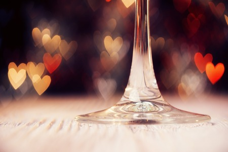 glass heart: Low angle view of wine glass over abstract defocused lights shaped like hearts