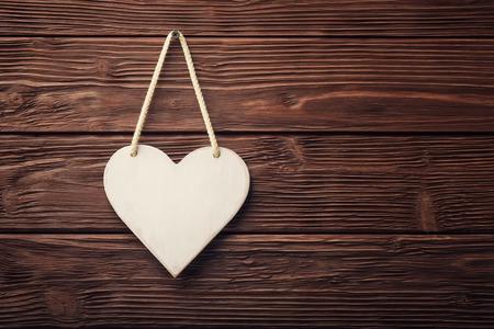 木製ヴィンテージ背景上にぶら下がっている白い心 写真素材