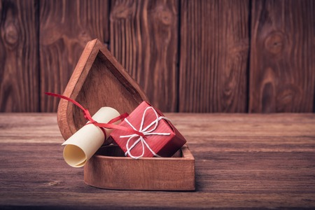 rolled paper: Rolled paper and gift box on Valentines day over defocused vintage wooden background