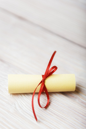 rolled paper: Rolled paper with red ribbon on white vintage wooden background