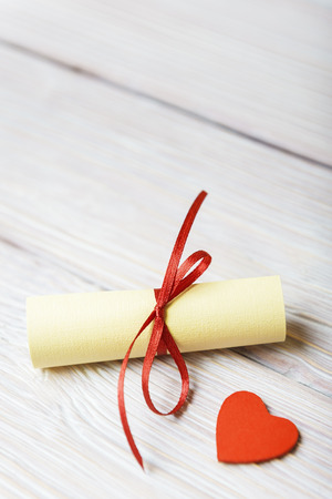 rolled paper: Rolled paper and red heart on vintage wooden background