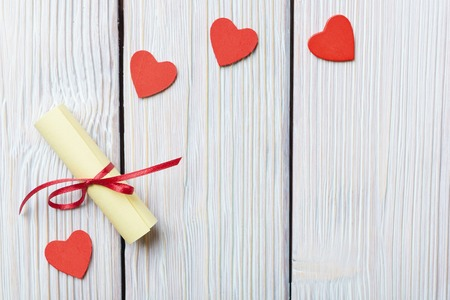rolled paper: Red hearts and rolled paper on vintage wooden background