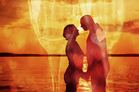 Double exposure of young romantic couple and glasses of champagne with heart shaped defocused lights photo