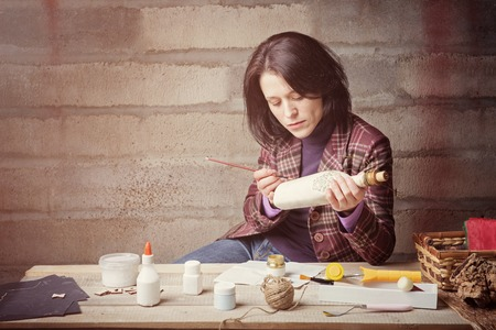 Woman is handcrafting a decorative bottle