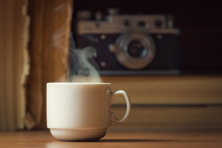Cup of hot coffee with steam over defocused books and vintage camera Stok Fotoğraf