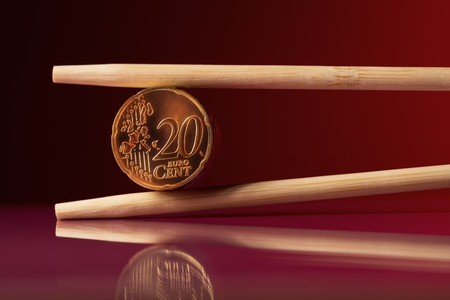 20 euro: Stack of 20 euro cent coins with chopstick over red background