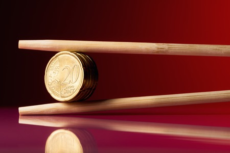 20 euro: Stack of 20 euro cent coins held by chopstick over red background Stock Photo