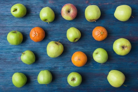 orange: Apples and oranges on old wooden background