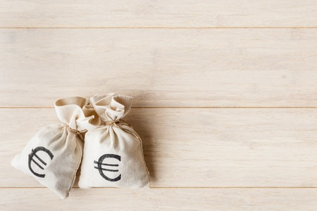 moneybag: Money bags with euro currency symbol on wooden background