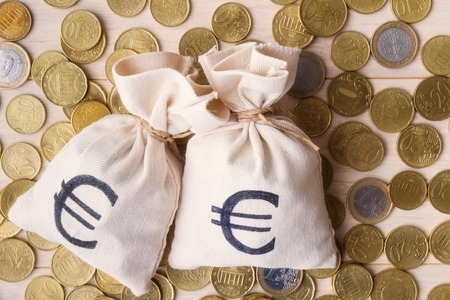 moneybag: Money bags and euro coins over wooden background, focus on money bags Stock Photo
