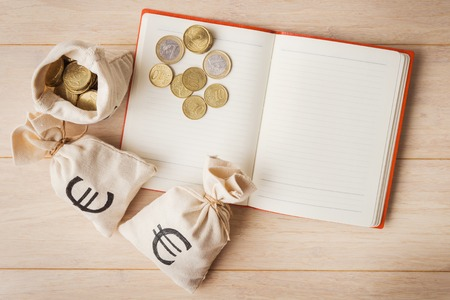 moneybag: Money bags with euro coins and open notebook on wooden background