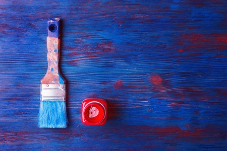 wood floor: Used paintbrush and jar with red paint on colored wooden background Stock Photo