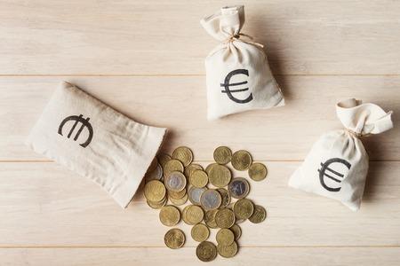 木製の背景、上面にお金袋でのユーロ硬貨