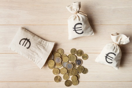 moneybag: Euro coins with money bags on wooden background, top view Stock Photo