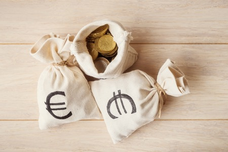 moneybag: Coins in money bags on light wooden background, top view Stock Photo