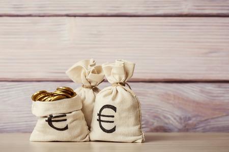 木製の背景にユーロ硬貨のお金の袋