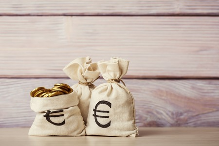 bag of money: Money bags with euro coins on wooden background Stock Photo