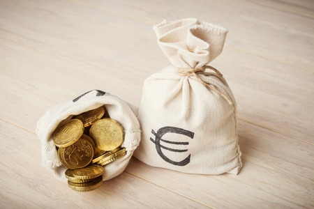 moneybag: Euro coins in money bags on wooden background
