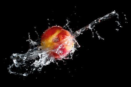 Raw nectarine in water splash over black background