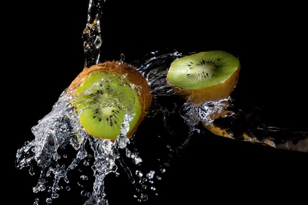 Kiwi slices with clear water splash on black background Stok Fotoğraf