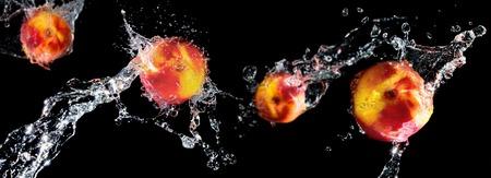 黒の背景に水のしぶきの桃 2 つ手前の果実に焦点を当てる