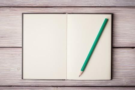 ノートブックを開くと古い木製机の上 pancil 写真素材