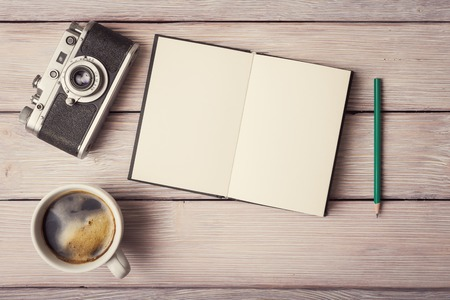 レトロなカメラ、開いているメモ帳と素朴な木製机の上のコーヒー カップ
