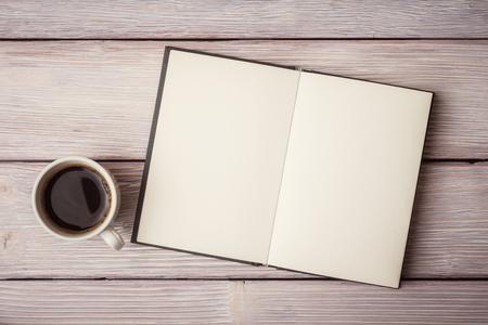 木製の机の上のコーヒー カップでノートブックを開く
