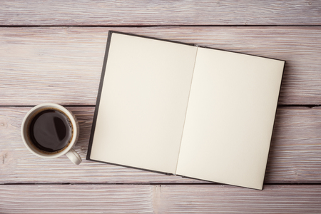 offen: Öffnen Sie Notizbuch mit Tasse Kaffee auf hölzernen Schreibtisch Lizenzfreie Bilder