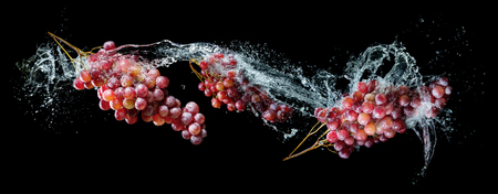 fruit drop: Grapes bunches in water splash over black background