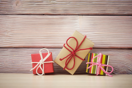 wrapped gift: Gift boxes over light wooden background