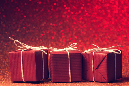three gift boxes: Three red gift boxes against defocused lights