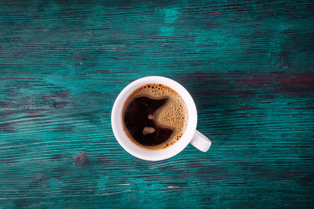 Top view of cup with coffee over old wooden background