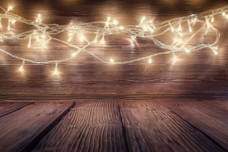 Xmas garland lights over rustic wooden background