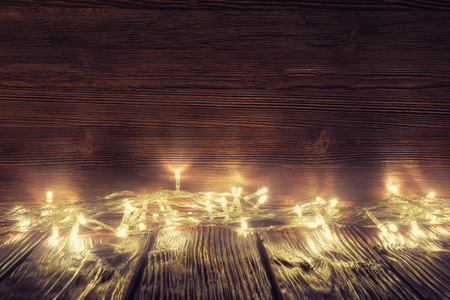 Christmas lights over old wooden background