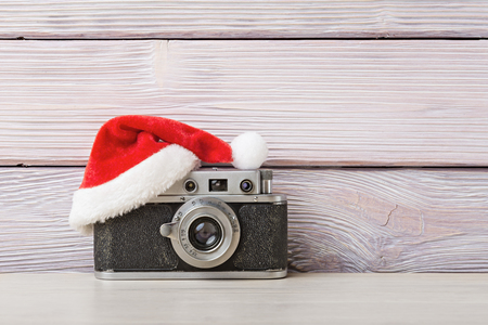 Old camera in santa hat on wooden background Reklamní fotografie