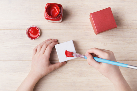 elementary age: Top view of  elementary age female hands during gift box painting Stock Photo