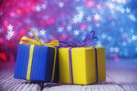 1 2 month: Blue and yellow gift boxes over defocused lights shaped as snowflakes