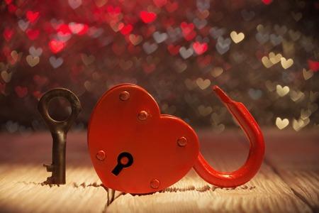 Unlocked hartvormige hangslot over abstracte Valentijnsdag achtergrond Stockfoto