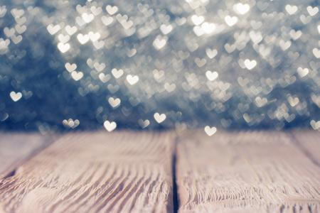 Vintage wooden  deck over heart shaped defocused lights. Shallow DOF Archivio Fotografico