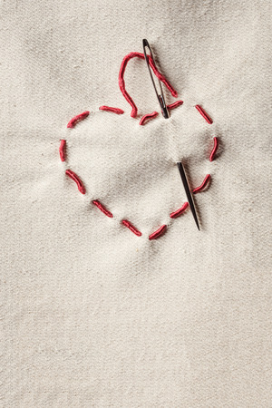 hilo rojo: Valentines heart symbol made of red thread over canvas background Foto de archivo