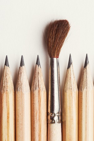 One brush among of pencils on light paper background Stock Photo
