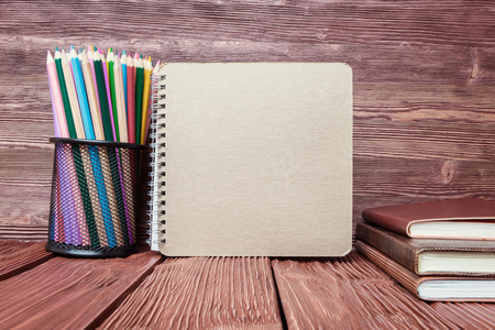 none: Cardboard, pencils and none pads over old wooden background