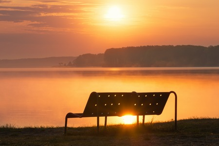 lake beach: Empty bench on lake beach over sunrise Stock Photo