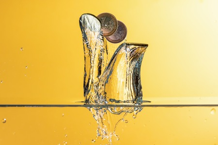 Euro coins with water splash over yellow background