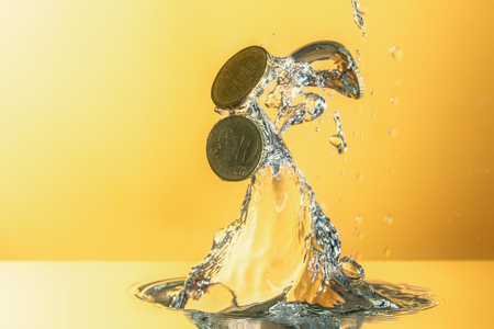 Euro coins moving from water with splash