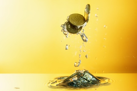 Euro coins with water splash